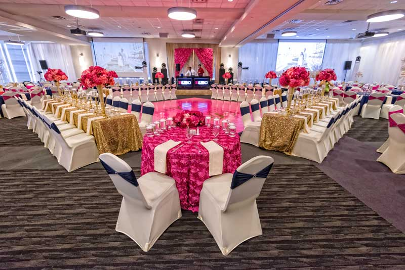 Red Oak Ballroom in Houston, CityCentre with covered chairs, table overlays, perimeter pipe and drape and uplighting