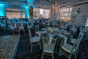 Frosty and beautiful silver and white Company Holiday Party set with silver bamboo chairs, textured table linens and candelabras at Houston, CityCentre