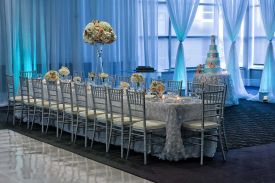 Gorgeous White Linens, Silver Bamboo Chairs, perimeter pipe and drape with Aqua Uplighting room setup at the Red Oak Ballroom in Houston, CityCentre