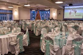 Elegant mint green and white Holiday Party set with chair covers, matching ties and table runners at Red Oak Ballroom Houston, CityCentre