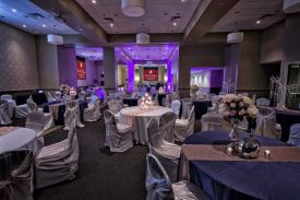 Elegant White and Navy Blue linens Decor with textured table runners and Purple Uplighting for a Wedding Reception at the Red Oak Ballroom B in Fort Worth, Sundance Square