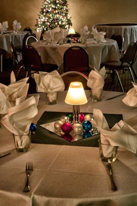 Festive and bright all white holiday party set with colorful balls as centerpiece