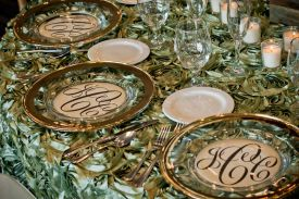 Ornate green Table Overlays with silver rimmed plate chargers at Red Oak Ballroom, Houston CityCentre