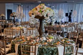 Ornate green Table Overlays with silver rimmed plate chargers, preset salads and gorgeous centerpieces at Red Oak Ballroom, Houston CityCentre