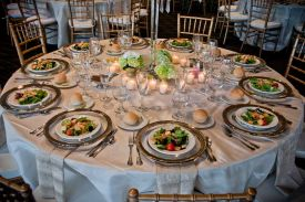 Elegant linens and bamboo chairs with silver rimmed plate chargers and preset salads at Red Oak Ballroom, Houston CityCentre
